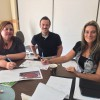 Three teachers work collaboratively at a table with their various work strategies on the table.