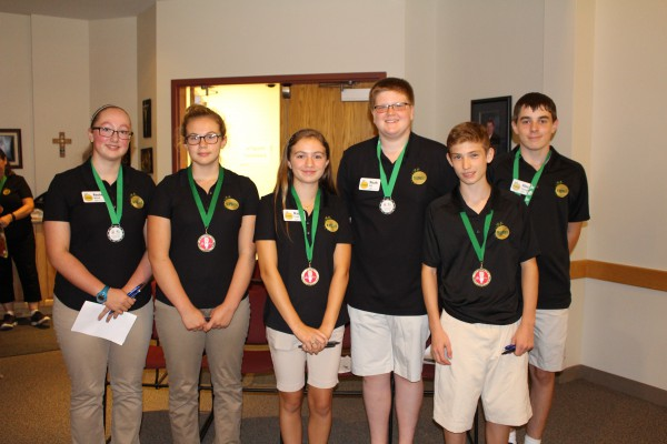 Group of six students stand smiling, wearing gold medals.