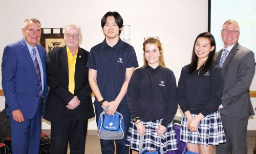 Three international students stand with the trustee, chair, and director of education at the CDSBEO board meeting on March 19.