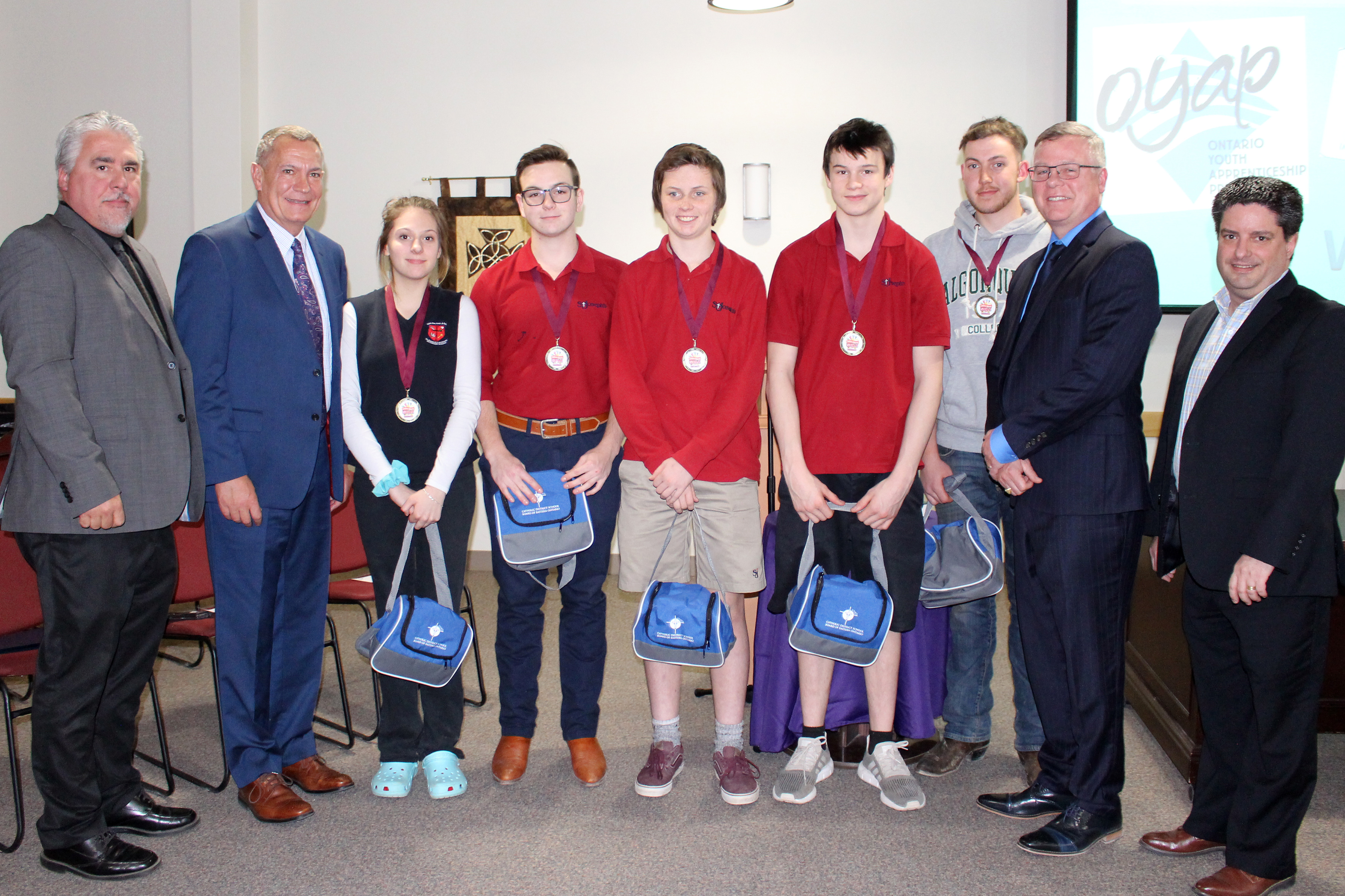 Students who attended the Eastern Ontario Skills Competition present information to the Board of Trustees. Students stand with board administrators and teacher.