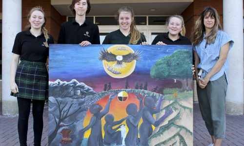 Students pose with a large painting.