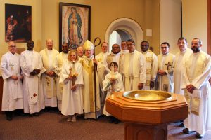 A group of clergy stand in a row at the CDSBEO board-wide mass.
