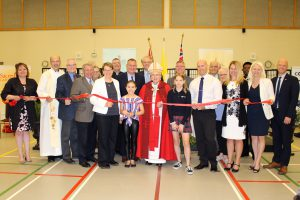A group of students, staff, clergy and dignitaries stand for the official ribbon cutting ceremony.