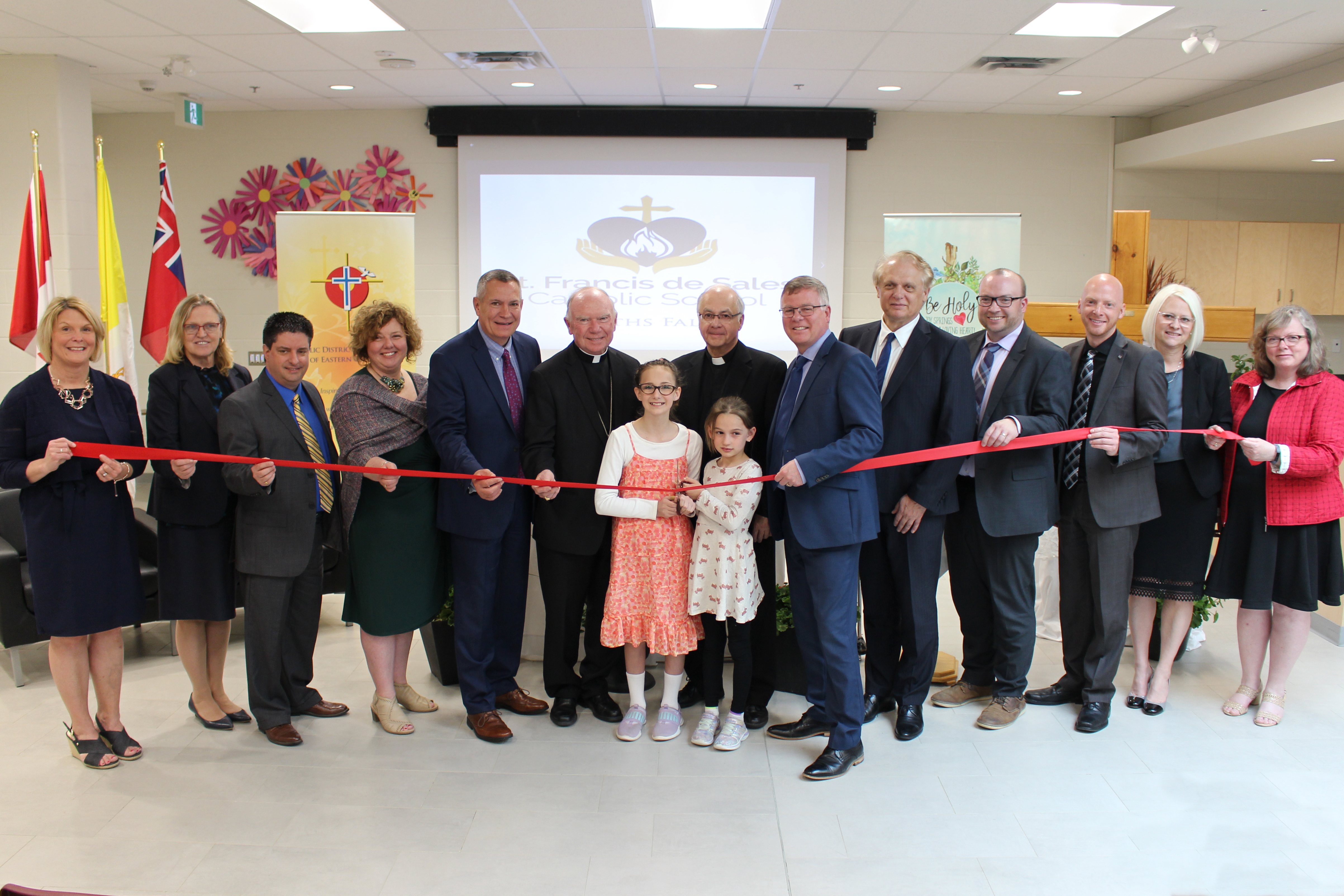 A group of staff, students, trustees and administrators cut the ribbon at the official opening of St. Francis de Sales Catholic School.
