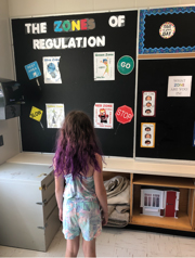 Child facing a blackboard in a classroom